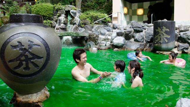 Eine junge Familie badet in grell-grünem Wasser, das mit Grüntee-Aroma versetzt ist.