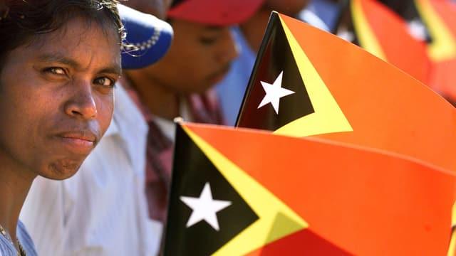 Unabhängigkeitsfeier in Osttimor im Jahr 2002: Menschen halten die Flagge.