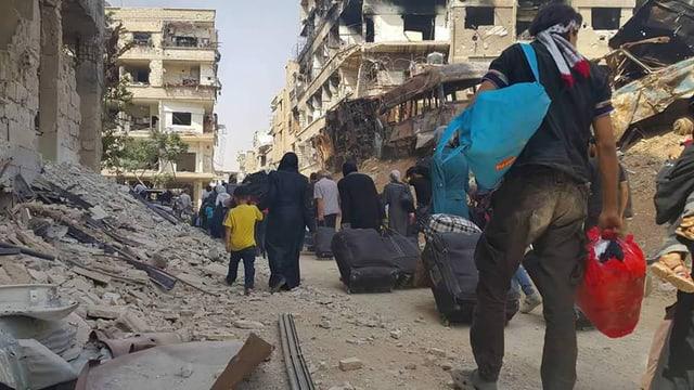 Syrische Familien mit Koffern und Taschen, sie verlassen einen komplett zerstörten Vorort von Damaskus.