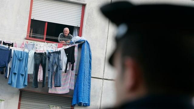 Carabinieri blickt auf Hausfassede, aus der ein Mann blickt.