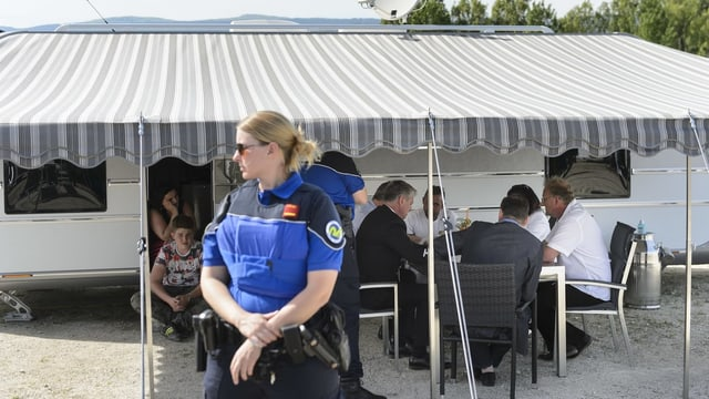 Purtret d'ina policista che protegia ina gruppa da roma che discurran.
