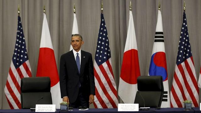Barck Obama allein hinter einem Konferenztisch mit Länderfahnen im Hintergrund