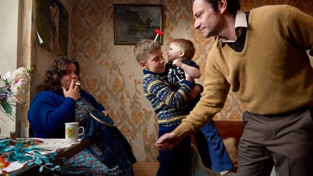 eine kleinfamilie in einem Zimmer.