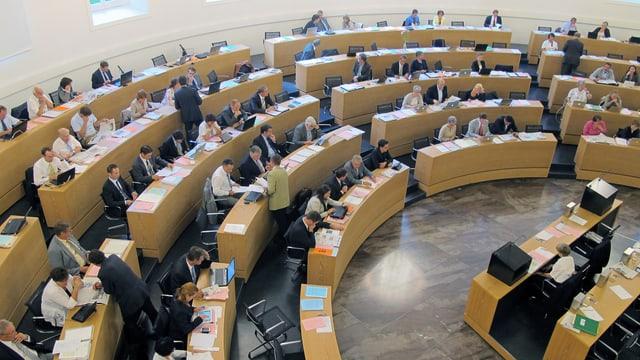 Im Halbkreis angeordnete Pulte mit Parlamentariern vor ihren Dokumenten.