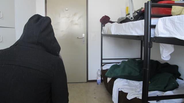 Ein Asylbewerber sitzt in einem Zimmer einer Asylunterkunft in der Region.