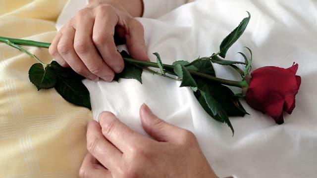 Ein verstorbener Mensch mit einer Rose in den Händen.