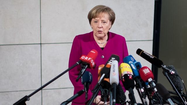 Angela Merkel avant microfons.