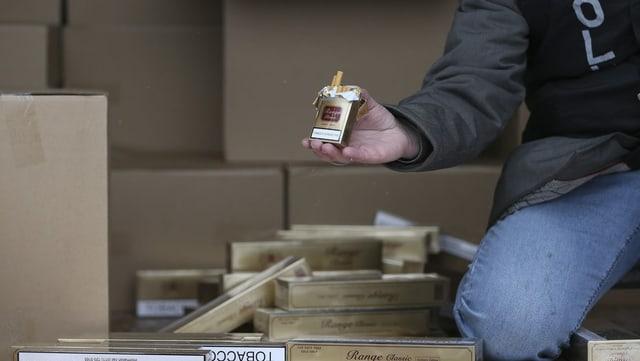 Ermittler hält Packung Zigaretten