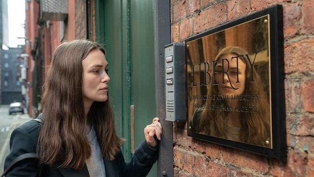 Katharine betrachtet ein Schild, das am Eingang der Anwaltskanzlei «Liberty» angebracht ist.