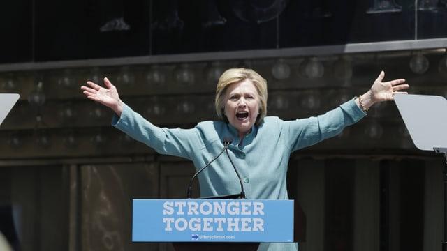 Clinton spricht von einem Podest herunter, die Arme weit geöffnet.