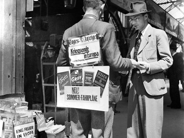 Ein Zeitungsverkäufer trägt Schilder mit den Schlagzeilen des Tages am 8. Mai 1945.