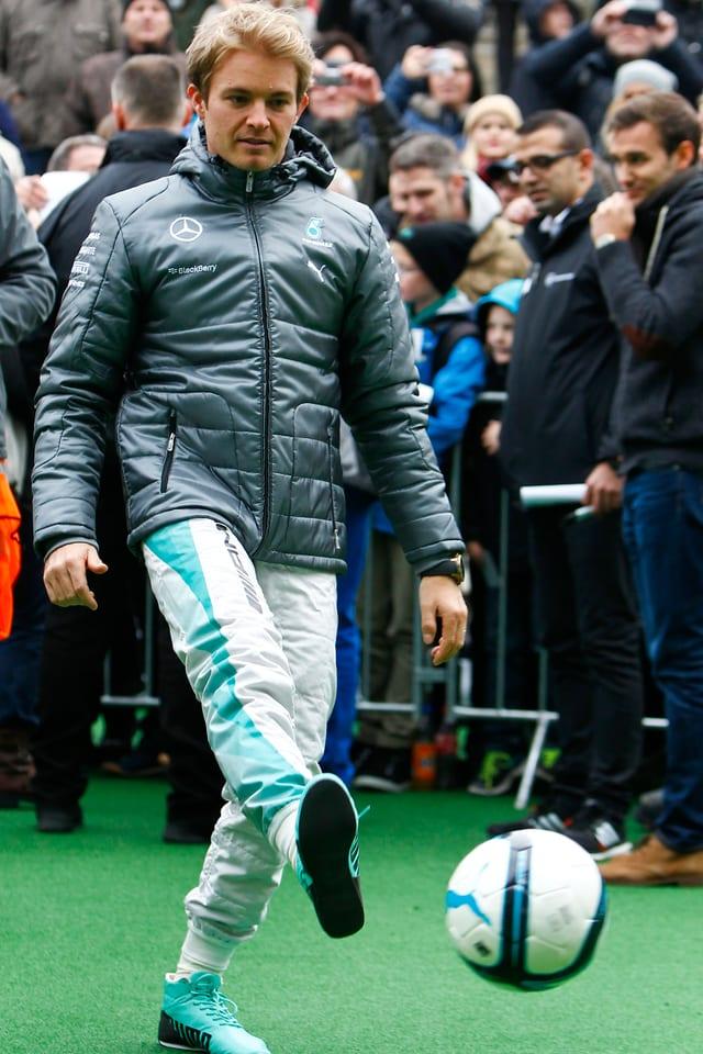 Nico Rosberg tritt einen Fussball.
