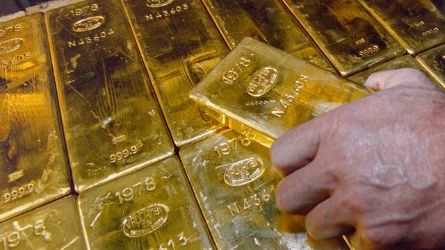 Ein Mann greift nach einem Goldbarren