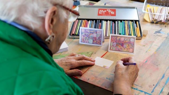 Eine Frau zeichnet mit Farbstiften.