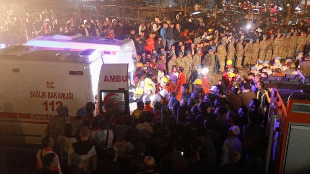 Zahlreiche Menschen auf Platz stehend, Ambulanz-Fahrzeuge