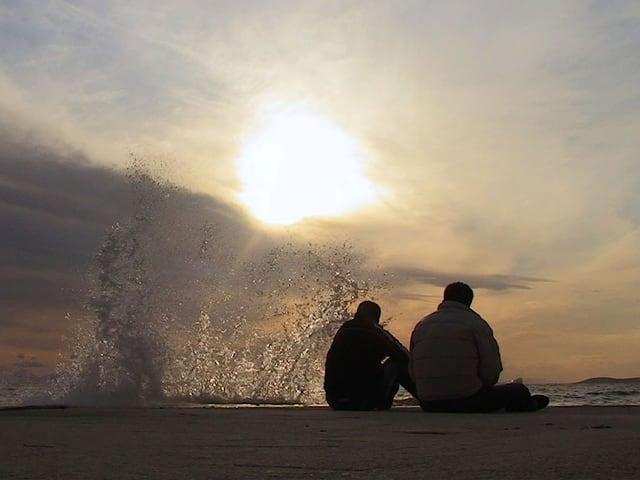 Zwei Flüchtlinge sitzen am Strand.