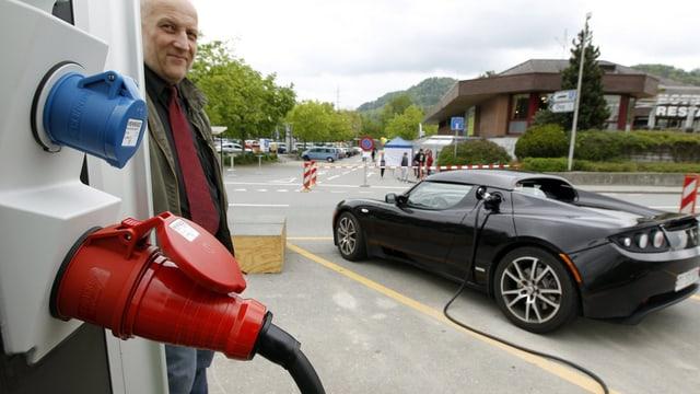 Ein Mann tankt sein Elektroauto.