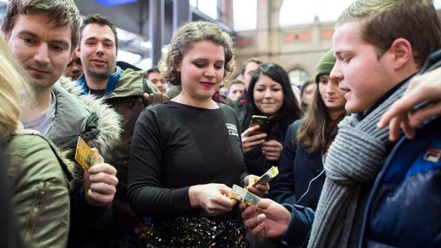 Eine Frau verteilt 10-Franken-Noten an Passanten im Hauptbahnhof Zürich.