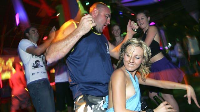In der Disko: Ein betrunkener Mann tanzt eine Frau von hinten an. Sie trägt ein luftiges, hellblaues Oberteil, das fast ihre Brust entblösst.