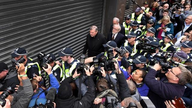 Polizisten beschützen mehrere schwarz gekleidete Männer, die an einer Journalistenmeute vorbeigehen.