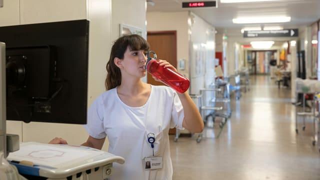 Aline Zehnder trinkt aus einer roten Flasche.