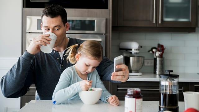 Ein Vater und seine Tochter sitzen in der Küche: Er schaut aufs Smartphone, das Kind isst.
