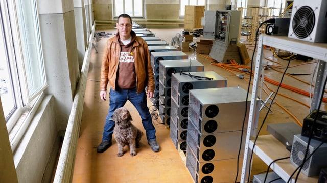 Ein Mann und sein Hund in einer Fabrikhalle; rechts Racks mit Rechnern.