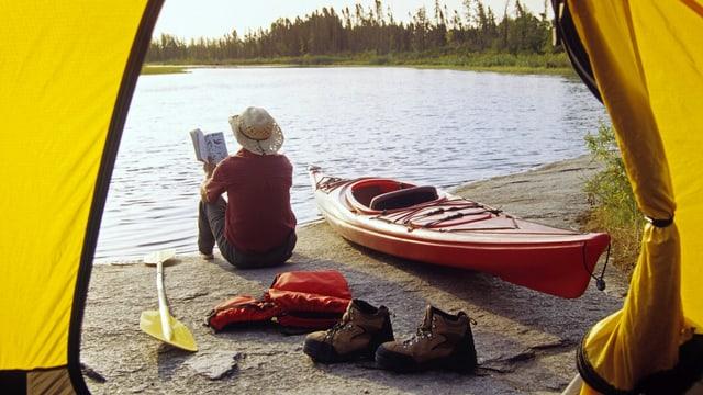 Ein Mann mit Hut sitzt vor seinem Zelt an einem See und liest ein Buch.