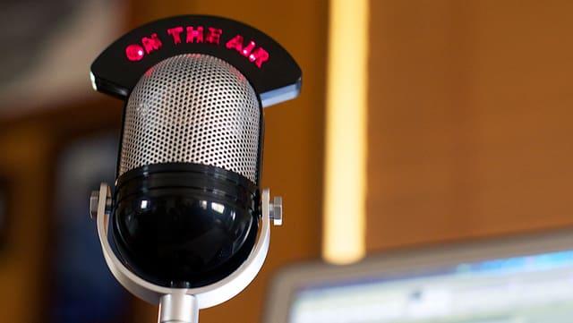 Ein Mikrofon steht vor einem – unscharf abgebildeten – Bildschirm.