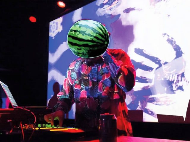 Ein DJ am DJ-Pult. Sein Kopf ist mit einer Wassermelone bedeckt.