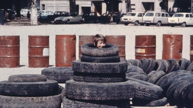 Stapel mit Autoreifen. Aus einem schaut der Kopf eines Jungen, im Hintergrund eine Reihe brauner Blechfässer.