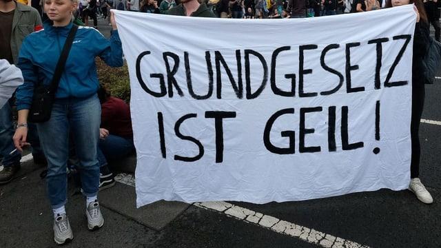 Eine junge blonde Frau an einer Demo mit einem Plakat, auf dem steht: Grundgesetz ist geil.