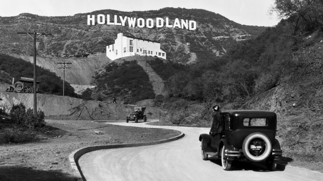 """Ein Auto fährt auf einer Strasse, dahinter an einem Hügel gross der Schriftzug: """"Hollywoodland"""" (s/w)."""