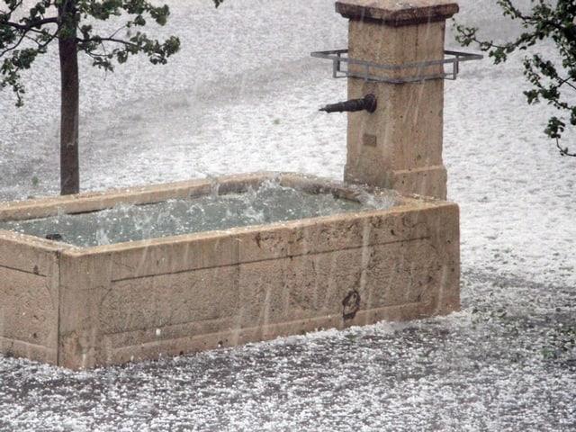 Ein Brunnen wird vom Hagel zugeschüttet.