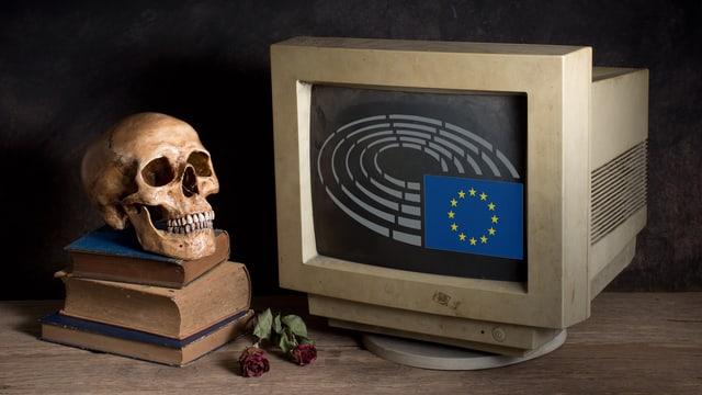 Ein Totenschädel steht neben einem Computerbildschirm, auf dem das Logo des Europäischen Parlaments zu sehen ist.