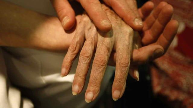 Eine Frau hält die Hand einer alten Frau.