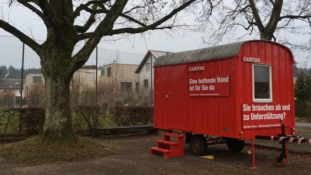 Roter Bauwagen neben einem Baum.