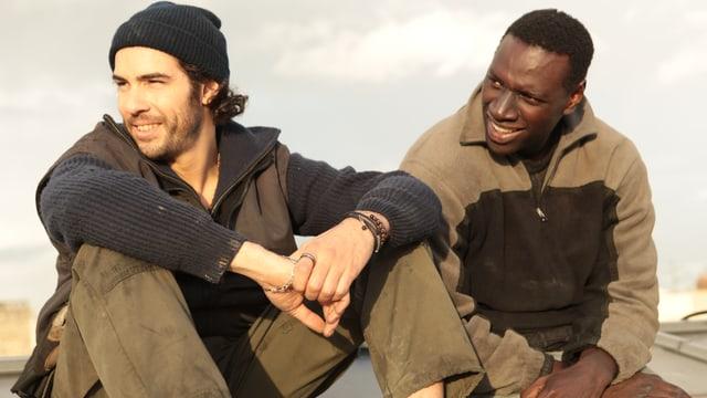 Zwei Männer sitzen auf einem Dach