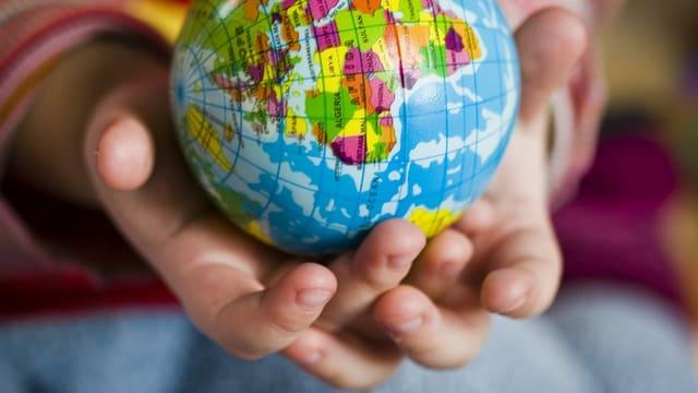 Ein Kind hält eine Weltkugel in der Hand.