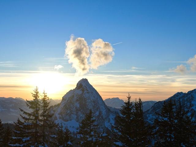 Gipfel mit herzförmiger kleiner Wolke darüber am blauen Himmel bei Sonnenuntergang