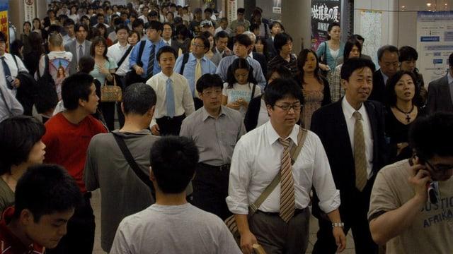 Menschen gehen durch die Gänge der U-Bahn in Tokio.