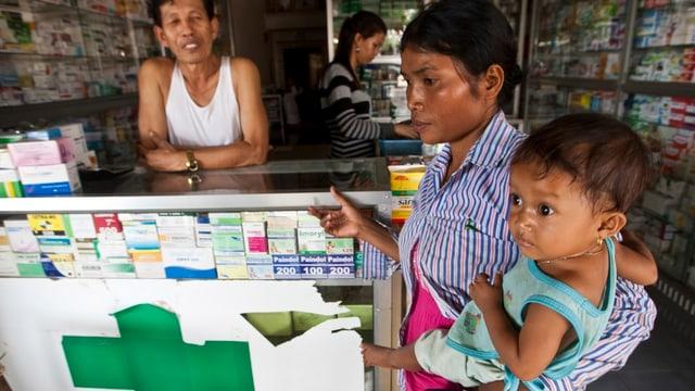 Asiatische Frau mit Kind in einer Apotheke.