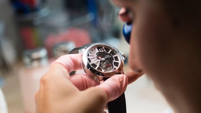 Uhrmacher von hinten fotografiert hält mit der linken Hand eine Uhr vor die Augen
