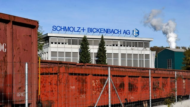 Güterwagen stehen vor einem Industriegebäude