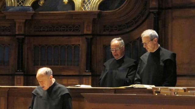 Drei Männer in Mönchskutten stehen singend hinter aufgeschlagenen Büchern.