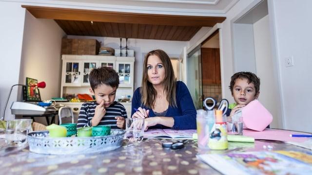 Eine Mutter sitzt am Wohnzimmertisch mit zwei Kindern.