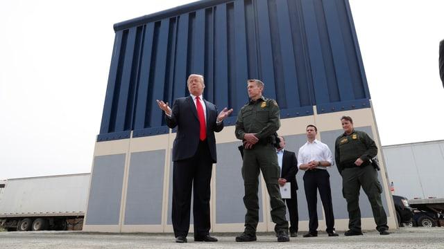 Trump mit Männern vor Mauerteil.