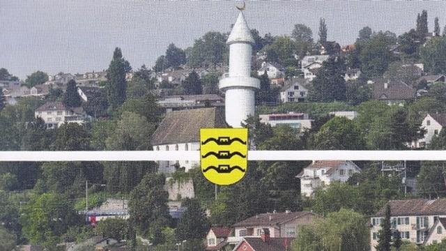 Dorf mit Minarett in der Mitte und Wappen