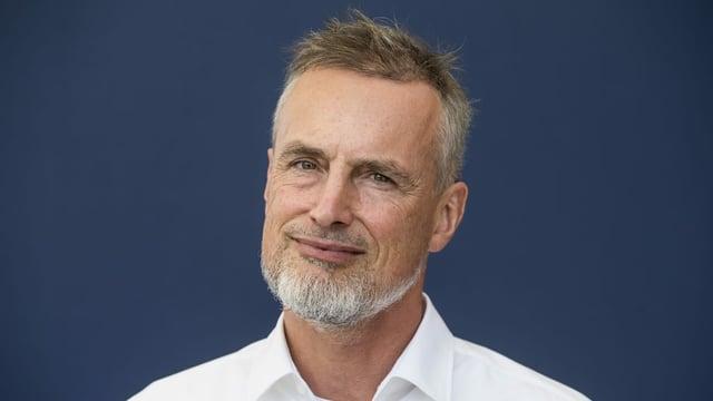 Jürgen Schmidhuber trägt ein weisses Hemd, einen Spitzbart und braunes, kurzes Haar.
