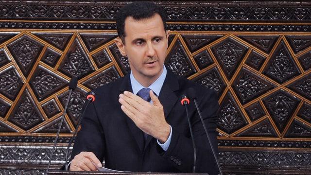 Assad hält eine Rede an einem Stehpult mit zwei kleinen Mikrofonen.